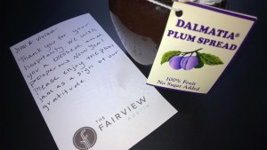 Photo of a handwritten note and gift of plum jam from guests