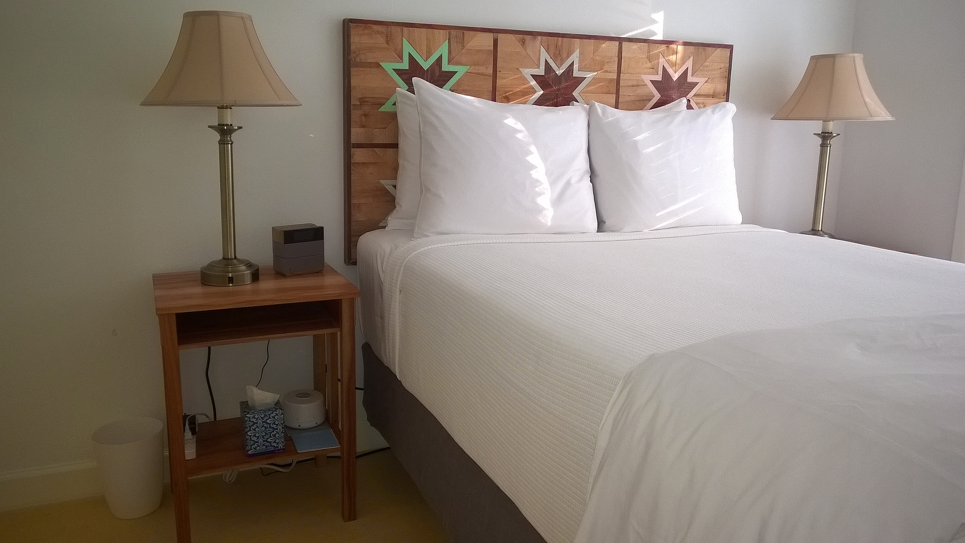 Photo of Queen Bed with custom inlaid wood headboard in the Carriage House