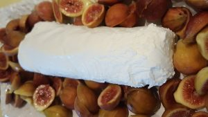 Fresh figs cut in half on serving plate with log of goat cheese on top